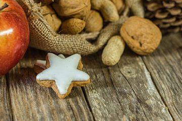 Kerstmaaltijd op tafel, noten, appel en stervormig koekje van Alex Winter