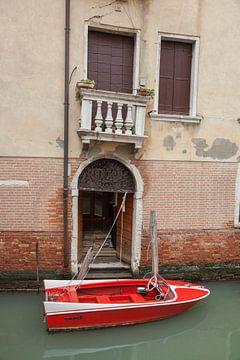 Oud pand en rode speedboot aan kanaal in oude centrum van Venetie, Italie van Joost Adriaanse