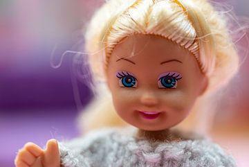 Une joyeuse poupée blonde en plastique