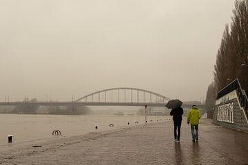 Twee wandelaars op half ondergelopen kade in Arnhem van Jan-Matthijs van Belzen