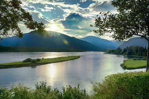 Zon gaat onder achter de bergen bij de rivier  van