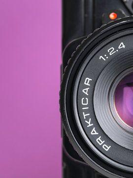 Makro-Nahaufnahme von Details einer alten 'Praktica'-Kamera mit violettem Hintergrund. von Iris Koopmans