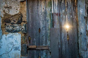 Le soleil à travers une fissure dans une porte sur Ellis Peeters