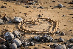 Romantisch hart getekend in het zand op het strand van