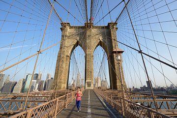 Brooklyn Bridge in New York in de ochtend met een hardloper von Merijn van der Vliet