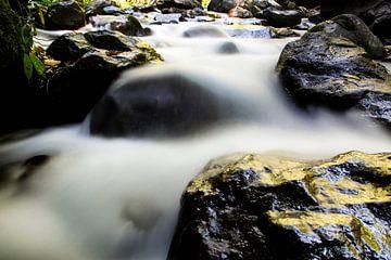 Rotsen onderaan de waterval op Lombok van Willem Vernes
