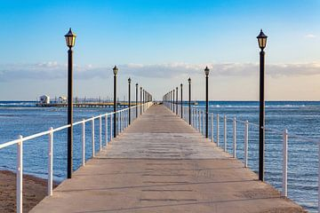 Lange rechte houten pier met lantaarnpalen aan de kust van Hurghada in Egypte van Ben Schonewille
