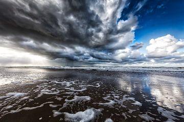 ondergaande zon met neerslag wolken boven de Noordzee van eric van der eijk