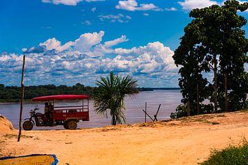 Spielendes Kind in einer Tuk-Tuk am Amazonasfluss von John Ozguc