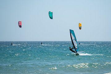 Surfer und Kitesurfer auf See in der Nähe von Tarifa, Spanien. von Monique van Helden