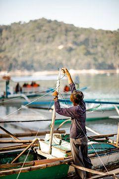 Un homme travaille sur son bateau aux Philippines sur Yvette Baur