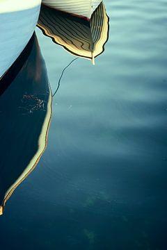 De boeg van een kleine vissersboot wordt weerspiegeld in het water van Michael Moser