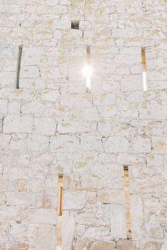Die Sonne scheint durch eine Öffnung in der alten Mauer einer Burg in Pals, einer mittelalterlichen  von Milou van Ham