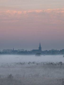 Dorf erhebt sich über den Nebel in den Niederlanden. von Wouter Bos