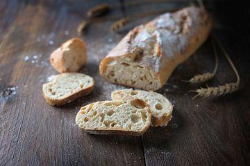 Frisches Baguette oder französisches Brot mit Zwiebeln gebacken, halbe Scheiben geschnitten, auf dun von Maren Winter