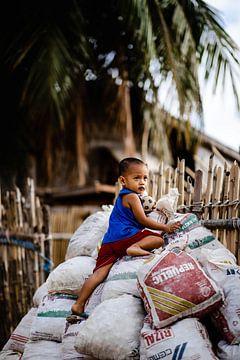 Un enfant joue sur des sacs de montagne, Philippines sur Yvette Baur