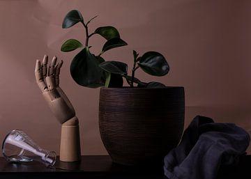 Stilleven met een omgevallen erlenmeyer, hand, plant en keukenhandddoek. van Angela Kiemeneij