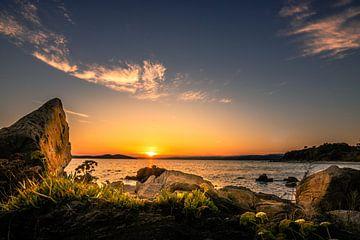 Zonsondergang aan de kust van Griekenland met strand en stenen en planten van Fotos by Jan Wehnert