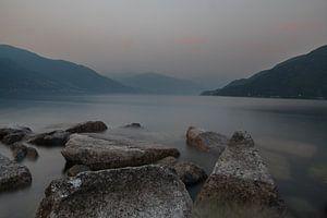 Avondschemer Lago Maggiore. Rotsblokken, water, nevel en bergen van