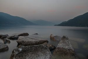 Avondschemer Lago Maggiore. Rotsblokken, water, nevel en bergen