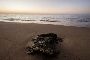 Zonsondergang op strand met steen van Marijn Goud