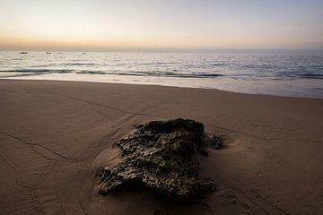 Zonsondergang op strand met steen