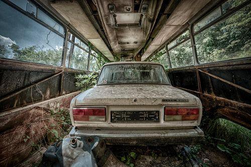 Oude vervallen auto Lada in een lege bus.