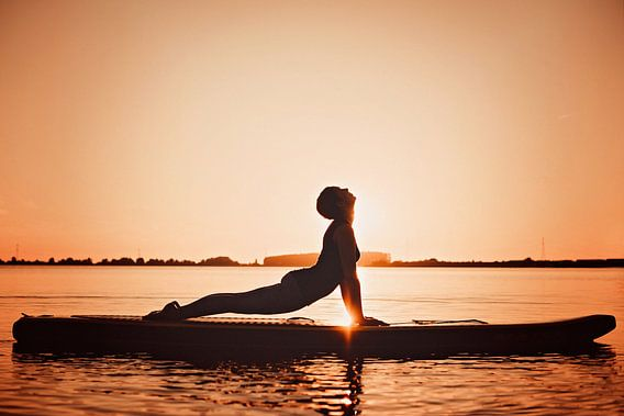 Yogapose als silhouette tijdens de ondergaande zon op een sup board
