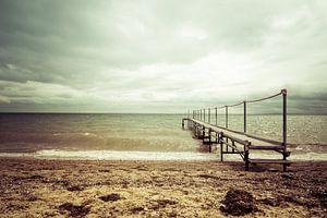 Steiger aan het strand bij een bewolkte lucht