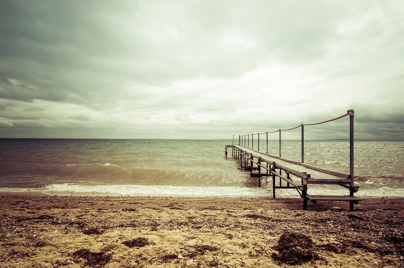 Steiger aan het strand bij een bewolkte lucht van Tony Buijse