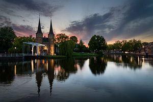 Gezicht op de Oostpoort, Delft bij zonsondergang van Jos Harpman