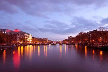 Stadsgezicht van Amsterdam bij avond in Nederland van Nisangha Masselink