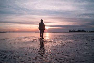 Prachtige zonsondergang met weerspiegeling op het zand van