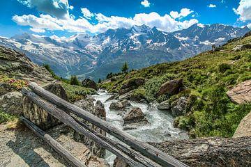 Brug over smeltwater, met uitzicht op de bergen boven Saas Fee van Maarten Salverda