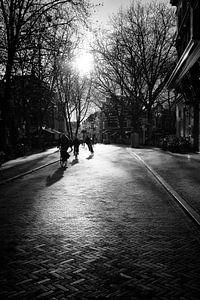 Tegenlicht in Utrecht: Drie fietsers en hun schaduw op de Mariaplaats in Utrecht