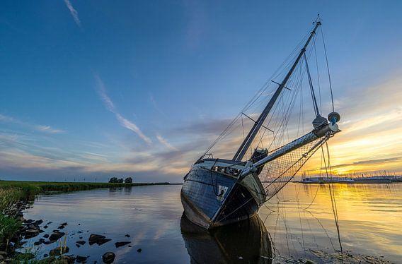 Een gestrande zeilboot bij Lemmer, tijdens zonsondergang van Roelof Nijholt