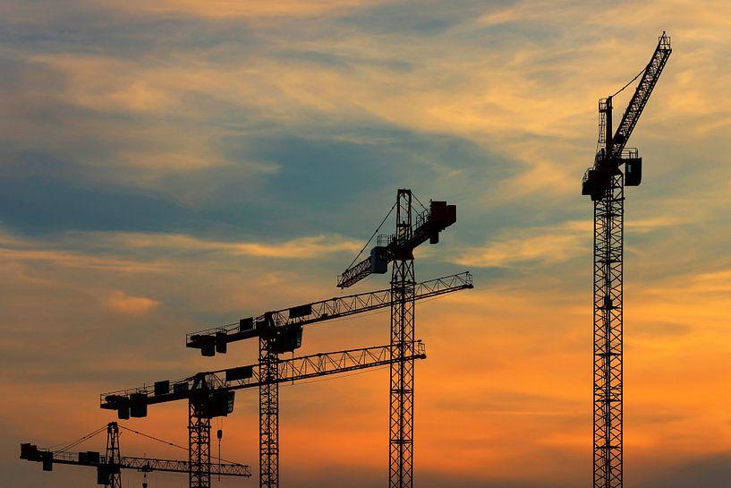 Grues de chantier au coucher du soleil sur Frank Herrmann