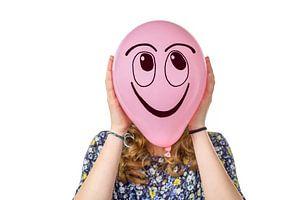 Roze ballon met lachend gezicht vastgehouden door tiener meisje.