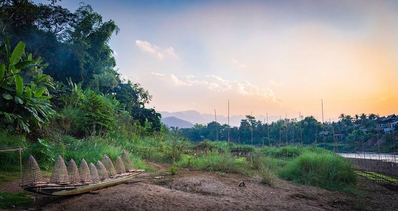 Bootje met viskorven aan de oever van de Nam Khan, Laos van Rietje Bulthuis