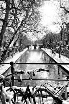 Besneeuwde fietsen op de Smeebrug over de Oudegracht in Utrecht in zwart-wit