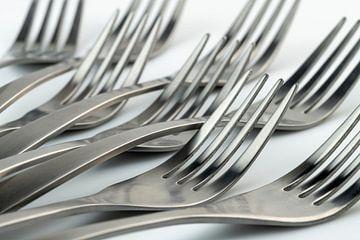 Abstracte artistieke foto van couvert, zijnde acht liggende vorken tegen een witte achtergrond van Tonko Oosterink