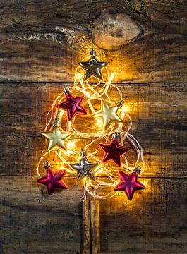 Kerstboomvorm met gouden en rode sterren en feestelijke lichtdecoratie van Alex Winter