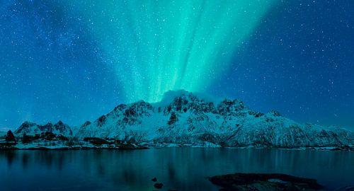 Noorderlicht boven een fjord en besneeuwde bergen in Noorwegen