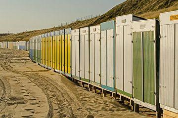 Strandhuisjes in scala aan kleuren op het strand van Tonko Oosterink