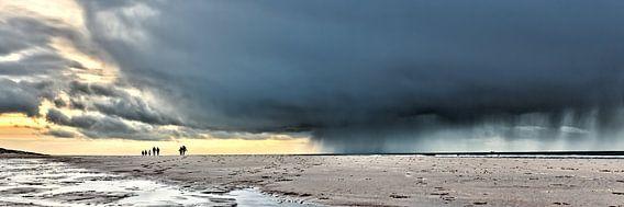 Donkere wolken met wandelaars op het strand