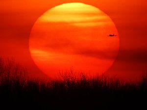 Zonsondergang met passerend vliegtuig