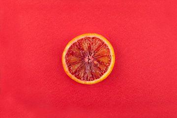 Schijfje bloedsinaasappel tegen rode achtergrond. van Ans van Heck