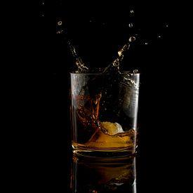 vallend ijsblokje in een glas whiskey van Compuinfoto .