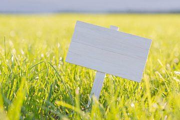 Wit bordje in een zonnige gras weide van Tonko Oosterink