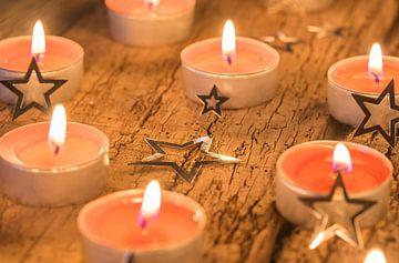 Brandende rode advents- en kerstkaarsen met stervormige ornamenten op hout van Alex Winter